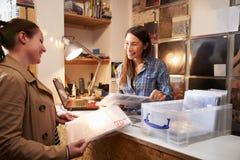 Client féminin étant servi au compteur d'une boutique record image libre de droits