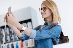 Client féminin blond prenant le selfie avec le smartphone de maquette au magasin Photo stock