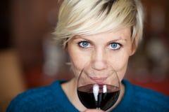 Client féminin buvant du vin rouge dans le restaurant Image stock