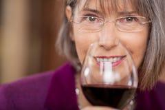 Client féminin buvant du vin rouge dans le restaurant Photographie stock libre de droits