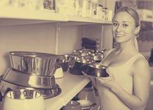 Client féminin choisissant des cuvettes pour des animaux familiers Photographie stock