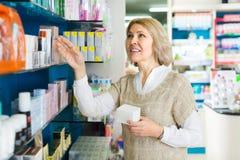 Client féminin dans la pharmacie de pharmacie photos stock