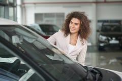 Client féminin de concessionnaire automobile choisissant l'automobile image stock