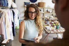 Client féminin de salutation de directeur de boutique dans la boutique image libre de droits