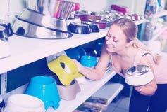 Client féminin de sourire choisissant des cuvettes pour des animaux familiers Photo stock