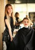 Client féminin de styliste en coiffure blond et de cheveux bouclés photos stock