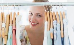 Client féminin heureux parmi le support de vêtements photo stock