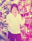 Client féminin regardant autour du fleuriste pour des usines pour acheter Images libres de droits