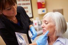Client féminin regardant dans le miroir après traitement de Botox images stock
