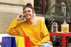 Client féminin s'asseyant dehors et à l'aide du téléphone portable image stock