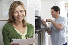 Client féminin satisfaisant avec Oven Repair Bill Photo stock