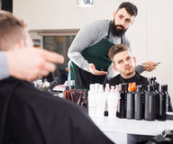 Client feeling discontent about his new haircut at hair salon Stock Photos