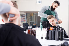 Client feeling discontent about his new haircut at hair salon Stock Image