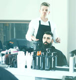 Client feeling discontent about his new haircut at hair salon. Young european client feeling discontent about his new haircut at hair salon Stock Photos