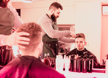 Client feeling discontent about his new haircut at hair salon. Young spanish client feeling discontent about his new haircut at hair salon Stock Photo