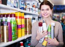 Client gai de femme décidant des produits de soins capillaires dans la boutique photo stock