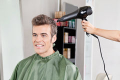 Client Gets His Hair Dried In Salon. Happy male client gets his hair dried after haircut in salon Royalty Free Stock Images