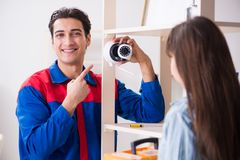 The client getting securty camera installed at home by contractor. Client getting securty camera installed at home by contractor Stock Photo