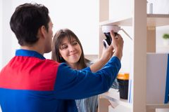 The client getting securty camera installed at home by contractor. Client getting securty camera installed at home by contractor Stock Photos