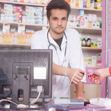 Client giving credit card to the pharmacist in the drugstore Stock Image