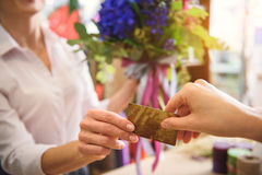 Client giving payment for flowers to saleswoman Stock Photos