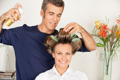Client With Hairdresser Setting Curls With. Portrait of female client with hairdresser setting curls with hairspray at salon royalty free stock photography