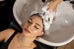 Client heureux dans un salon de coiffure qui se lavent les cheveux avec le shampooing photographie stock libre de droits