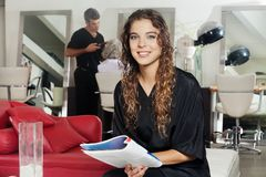 Client Holding Magazine With Hairdresser Working. Portrait of female client holding magazine with hairdresser working in the background at hair salon Royalty Free Stock Photos