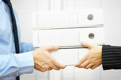Client Is Passing Documentation In Binders To His Partner Royalty Free Stock Image