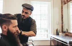 Client élégant de portion de coiffeur à sa boutique Photographie stock