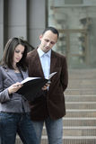 Client looking at contract. Client looking at a contract outdoors next to a business man Stock Photography