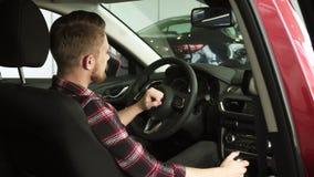 Client masculin beau joyeux montrant des pouces se reposant dans une nouvelle voiture au concessionnaire banque de vidéos