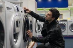 Client masculin choisissant la machine à laver images stock