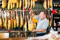 Client masculin choisissant le jamon espagnol Images stock