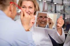 Client masculin de consultation d'opticien féminin blond avec du charme au sujet de f Photo libre de droits