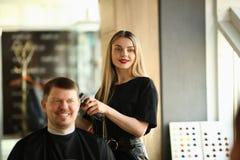Client masculin de sourire de rasage de styliste en coiffure de jeune fille image stock