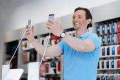 Client masculin enthousiaste prenant le selfie avec le téléphone deux au magasin Photo libre de droits
