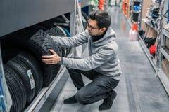 Client masculin futé choisissant de nouveaux pneus dans le supermarché image stock