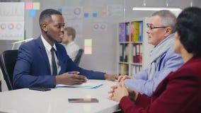 Client masculin mûr en verres serrant la main à l'avocat banque de vidéos