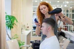 Client masculin obtenant la coupe de cheveux La coiffeuse de fille sèche mes cheveux un jeune, attirant type dans un salon de bea images libres de droits