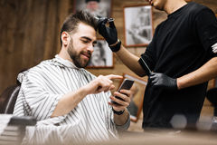 Client messaging. Gloved hairdresser serving his client with smartphone Royalty Free Stock Image