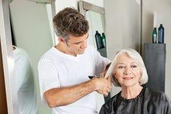 Client obtenant la coupe de cheveux par le styliste en coiffure Image stock