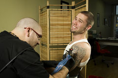 Client in pain getting a tattoo Royalty Free Stock Images