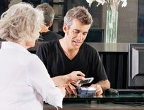 Client payant par le téléphone portable au salon Image stock