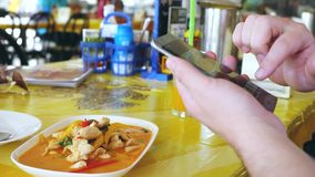 Client photographs liked the dish on a mobile phone. Take a photo of tom yam thai soup in a restaurant with mobile phone stock footage