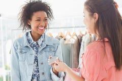 Client recevant la carte de crédit de la vendeuse photo stock