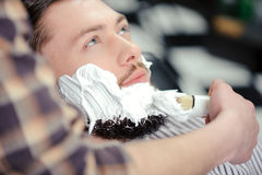 Client shaving at barber shop stock photography