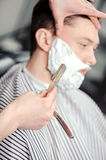 Client shaving at barber shop royalty free stock photography
