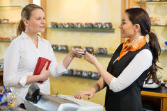Client at shop paying at cash register. With saleswoman Royalty Free Stock Photos
