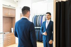 Client Showing Contentment About New Suit. Reflection of Hispanic customer smiling while wearing new suit in rental store royalty free stock photo
